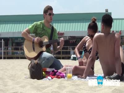 ბიჭი რომელიც პლიაჟზე მყოფ შიშველ გოგოებს თავს სიმღერით აწონებს